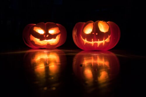 Carved pumpkins for Halloween lit up with candles in the dark